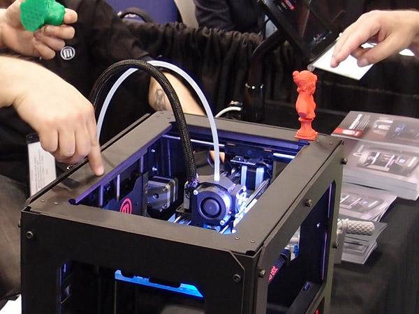 """Pohled do útrob designově vyladěného MakerBot Replicatoru 2. To modré světlo nemá žádný praktický význam, prostě je """"cool"""". Barva se dá změnit výměnou osvětlovacích diod. Foto: Jan Homola"""