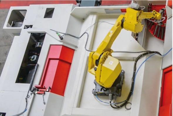 Robot podává z rotačního zásobníku polotovary.